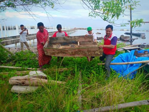 Bahu membahu menggotong perahu yang sudah rusak dihempas tsunami